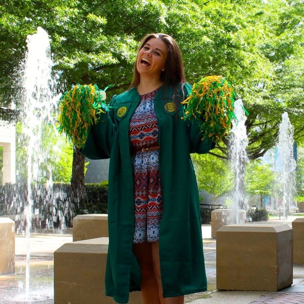 A photo of Alexis Patullo in her graduation gown for George Mason University. Alexis is standing in front of a fountain and holding green and yellow pom-poms.