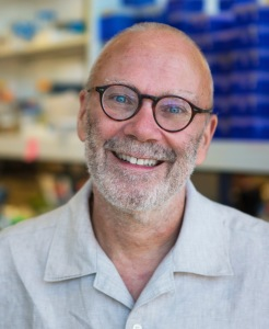 This is a headshot style photograph of Dr. Gary Pielak in a grey button down shirt with glasses. He is smiling at the camera.