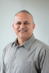 This is a headshot style photo of Dr. Dave Thirumalai in a grey striped button down shirt. He is smiling at the camera.