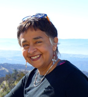 This is a headshot style photograph of Dr. Devaki Bhaya smiling at the camera with glasses on her head. Wearing silver jewelry and a black shirt, she is standing in front of forest covered mountains.