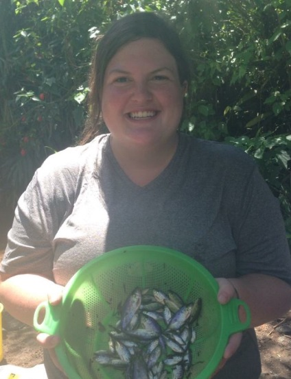Grace is looking into the camera and smiling. There are tropical trees in the background and she is wearing a gray tshirt and holding a green sive full of Rhoadsia altipinna, a small western Ecuadorian Tetra fish which appear rainbow.