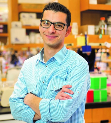 Dr. Ahmad Khalil is smiling, arms crossed, standing in front of his lab bench while wearing a blue and white checked shirt and glasses.