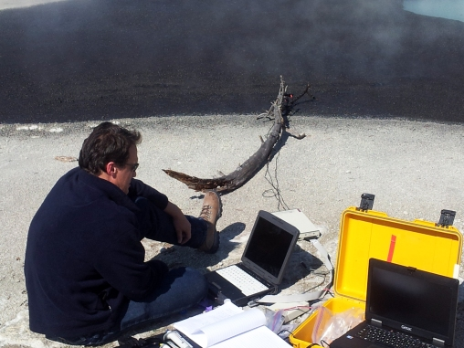 EJ is sitting on the ground in front of a laptop, several open books and papers, as well as boxes and electrical equiptment. He is sitting in sand near a large log and has electrodes connected to wires several feet away in an expanse of smoldering ash.