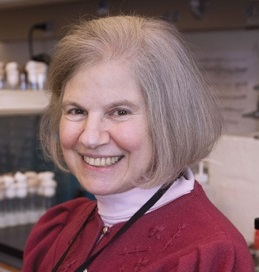 This is a headshot style photo of Dr. Susan Gerbi who is sitting in her laboratory in front of culture test tubes and a white board, wearing a red sweater, pink turtleneck shirt, and smiling.