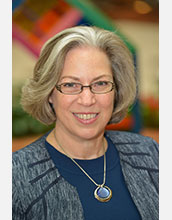 A headshot style photograph of Dr. Tornow, she has short grey hair and is wearing black glasses, a blue suit, and a blue necklace.