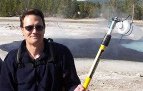 EJ is smiling into the camera with sunglasses, he is holding a large metal stick with a sampling bottle attached and a hot spring is steaming in the background