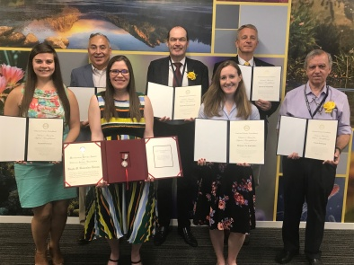 The NSF directors award winners are standing together holding their certificates and smiling