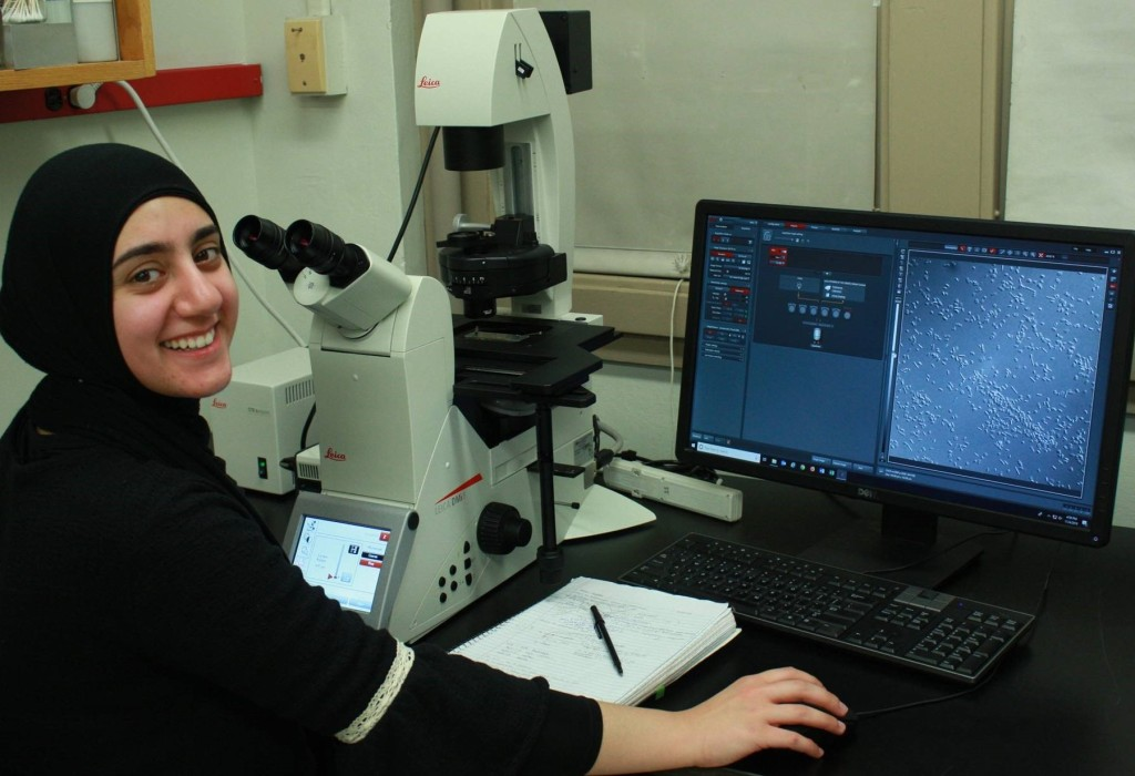 Dr Pohlschroder's graduate student in front of a microscope next to a computer with biofilm samples displayed on the screen